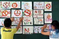 Children are posting anti-smoking banners on the wall as China's