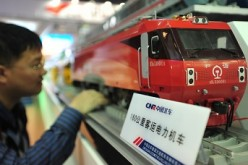 A visitor takes a look at a model locomotive train made by China CNF at an exhibition in Beijing.