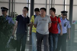 The suspected leader of a gang that allegedly hired university students to impersonate test takers for the gaokao is escorted by officers in a train station in Heze City, Shandong Province, on June 8.