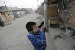 A child aims his toy gun at something as he plays in a poor neighborhood in Beijing.