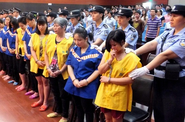 Handcuffed child traffickers are presented in court.