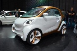 People look at a smart car on display in Guangzhou Auto Show.