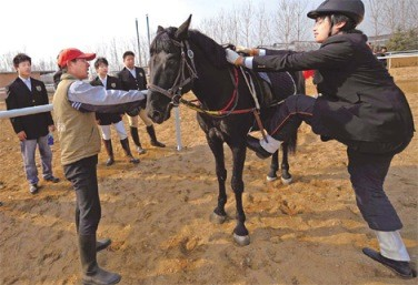 A student learns how to mount a horse from a trainer in a riding club in Changping.