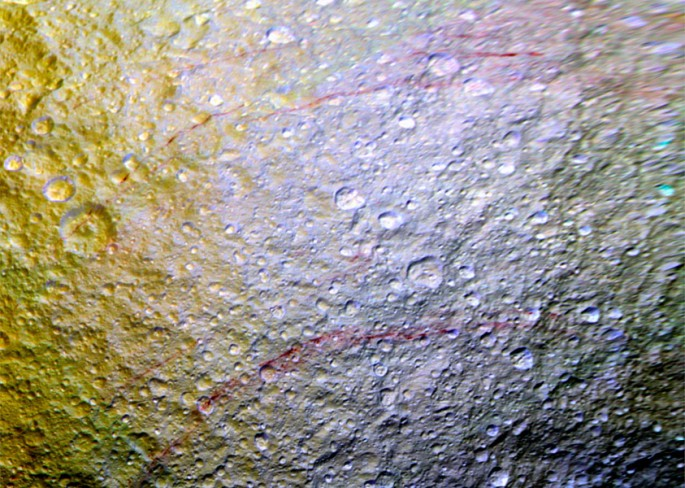 Unusual arc-shaped, reddish streaks cut across the surface of Saturn's ice-rich moon Tethys in this enhanced-color mosaic. The red streaks are among the most unusual color features on Saturn's moons to be revealed by Cassini's cameras.