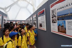 Youth visit a photo exhibition on World War II at National Aquatics Center in Beijing, Aug. 4, 2015.