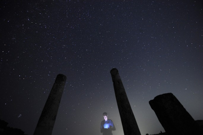 A photographer looks at his camera during the Perseid meteor shower at Stobi archeological site, which was the largest city in the northern part of the Roman province Macedonia and later capital city of the Roman province Macedonia Secunda, early August 1