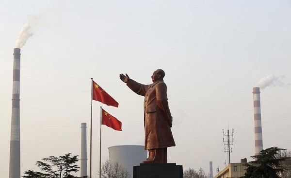 Smoke comes out of the chimneys of Wuhan Iron and Steel Corp. in Wuhan, Hubei Province, where a statue of Mao Zedong stands.