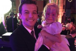 One Direction's Louis Tomlinson carries Eleanor Stollery, a girl  with brain tumour who had lost her eyesight, during the recent Believe in Magic Charity Ball.