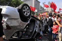 Demonstrators hold Chinese flags and banners beside an overturned car of a Japanese brand during a protest in Xi'an, Shaanxi Province, in this Sept. 15, 2012 file photo.