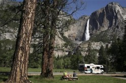 A family has a picnic in view of Upper Yosemite Falls in Yosemite National Park, California.