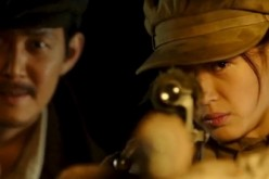 Jun Ji-hyun aims at a target while Lee Jung-jae observes in the background in the film