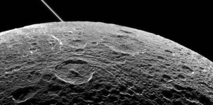 A view of Saturn's moon Dione captured by NASA's Cassini spacecraft during a close flyby on June 16, 2015. The diagonal line near upper left is the rings of Saturn, in the distance.