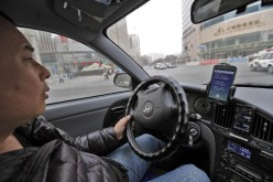 A taxi driver checks his two smartphones for potential customers in Beijing, Feb. 18, 2014.