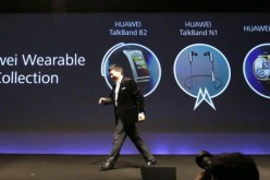Huawei chief executive Richard Yu walks past his presentation on Huawei's wearable collection.