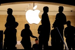 Customers stand beneath an Apple logo.