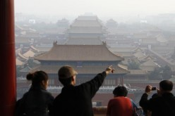 Tourists look over the Forbidden City from Jingshan Park in Beijing, Oct. 13, 2009.