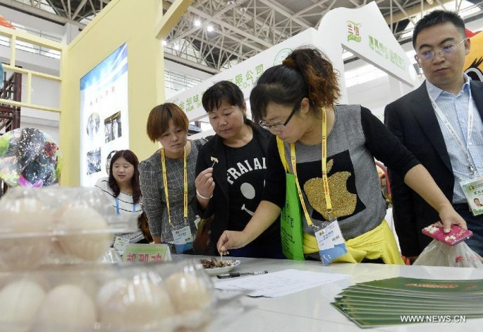 Women sample food at the China-Arab States Expo 2015 in Yinchuan.