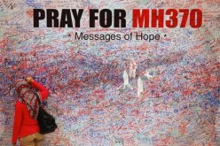 A woman leaves a messages of support and hope for the passengers of the missing Malaysia Airlines MH370 in central Kuala Lumpur March 16, 2014.
