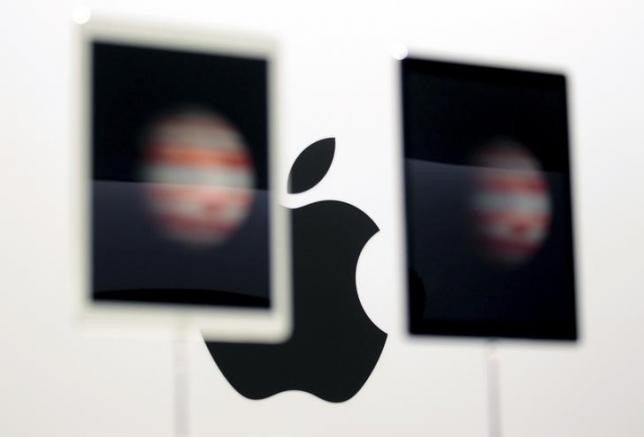 The Apple logo is seen behind a pair of Apple iPad Pros on display in San Francisco, California, Sept. 9, 2015.