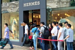 Chinese tourists line up outside an overseas Hermes store.