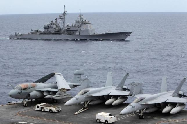 U.S. fighter jets stand by at the upper deck of a USS George Washington aircraft carrier while a U.S. Cowpens ship passes by the South China Sea, Sept. 3, 2010.
