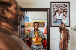 A man holds a bust of Mao Zedong, the former chairman of the Communist Party of China, inside a souvenir shop in Shaoshan, Mao's birthplace.