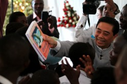 Lu Junqing, chairman of the China-Africa Project Hope, hands books to Hope School students in Nairobi, Kenya, Sept. 30, 2015.