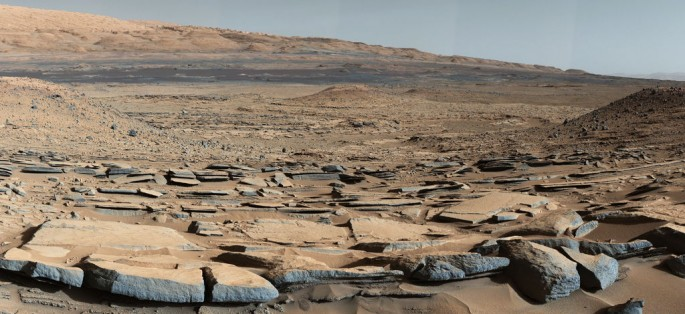 "A view from the ""Kimberly"" formation on Mars taken by NASA's Curiosity rover. The strata in the foreground dip towards the base of Mount Sharp, indicating the ancient depression that existed before the larger bulk of the mountain formed."