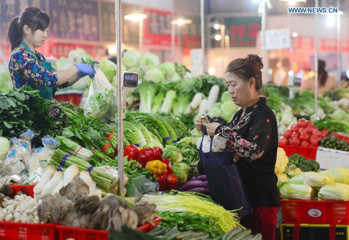 A resident purchases vegetables at a market in Shijiazhuang, north China's Hebei Province, Oct. 13, 2015.