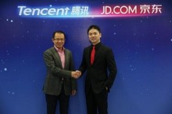 Martin Lau, president of Tencent, and Richard Liu of JD.com shake hands during the announcement of their strategic partnership in e-commerce in March.