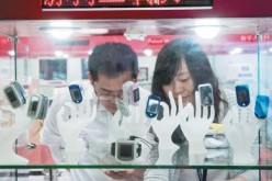 Visitors look at the smart bands and wearable devices displayed at an information technology expo in Shenzhen.