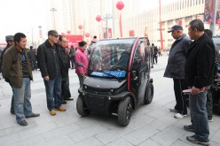 People look at a BIRO City electric vehicle at Wanda Plaza, Yantai, Shandong Province, on Nov. 21, 2014.