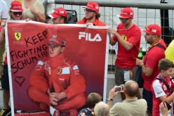 A man takes a photograph of Scuderia Ferrari's supporters as they hold a banner with Michael Schumacher's photo on it.