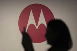 A user checking out her phone against the backdrop of the Motorola logo.