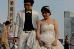 A newlywed couple walk down the stairs after posing for pictures at the Bund in central Shanghai.