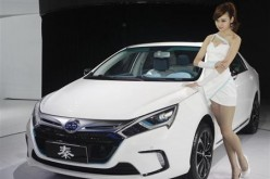 A model stands next to China's BYD QIN at Auto China 2012 in Beijing.