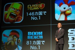 Billionaire Masayoshi Son, chairman and chief executive officer of SoftBank Corp., speaks in front of mobile game images of Clash of Clans and Boom Beach by gamemaker Supercell Oy during a news conference in Tokyo, Japan, on Friday, Aug. 8, 2014.