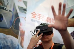 A man, donning the Oculus Rift development kit 2, tries to
