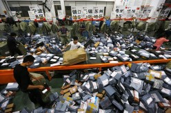 Workers deal with express packages at an assembly line in Wenzhou, Zhejiang Province, Nov. 12, 2014.