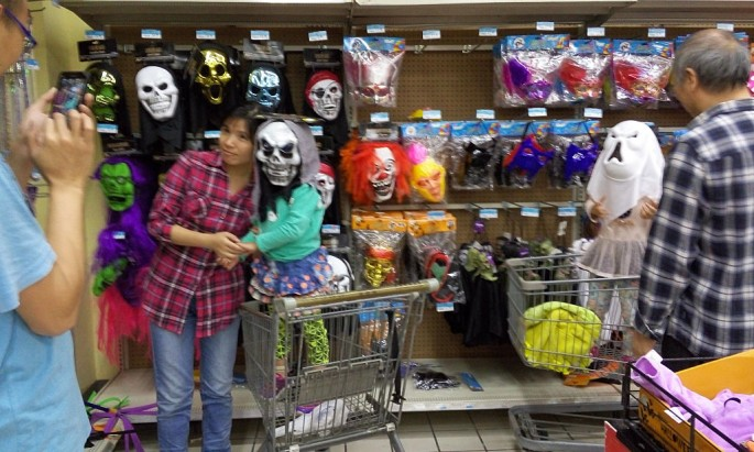 A mother carries her son while the boy wears a Halloween mask at a shopping store in Wuhan, Hubei Province, Oct. 26, 2015.