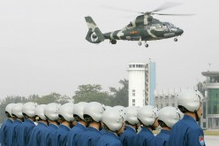 Outgoing Chinese People's Liberation Army (PLA) helicopter pilots watch as a helicopter full of new air force personnel arrives at a ceremony in Hong Kong on Nov. 25, 2007.
