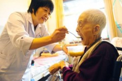 A caregiver attends to an elderly at a nursing home in Jinan, capital of Shandong Province.