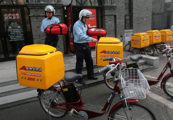 Employees carry delivery containers to their bicycles in Nanjing, Jiangsu Province, Jan. 18, 2007.