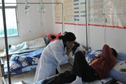 A doctor helps a patient at a clinic in Guangsong Village of Dai-Jingpo Autonomous Prefecture of Dehong, southwest China's Yunnan Province, Nov. 17, 2011.