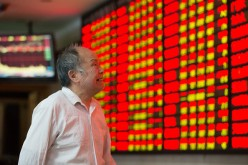 An investor observes stock market at a stock exchange hall in Nanjing, Jiangsu Province, on Oct. 20, 2015.