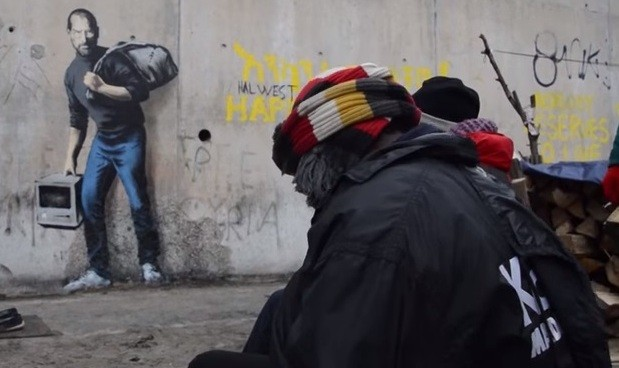 Migrants in a refugee camp in Calais, France see the Steve Jobs graffiti art created by English street artist Banksy.
