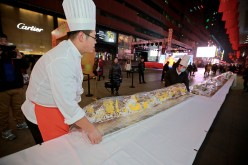 Workers carry a 21-meter-long cake for charity sale at a hotel during the lighting ceremony for 2015 Christmas in Shenyang, Liaoning Province, on Nov. 27, 2015.