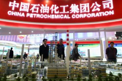 Chinese visitors look at a model of the China Petrochemical Corporation (Sinopec) at an expo in Beijing on March 21, 2009.