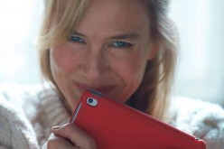 Renée Zellweger smiles while clutching an iPad.
