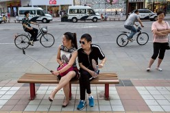 A Chinese couple takes pictures of themselves as they sit at a shopping district in Beijing, China.
